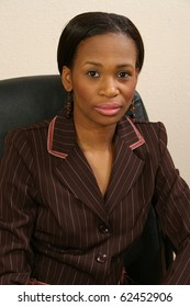Beautiful 25 year old african american woman in suit portrait in office chair.