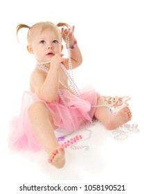 A beautiful 2-year-old with multiple strands of pink and white pearls.  She's wearing a shear pink tutu.  On a white background.