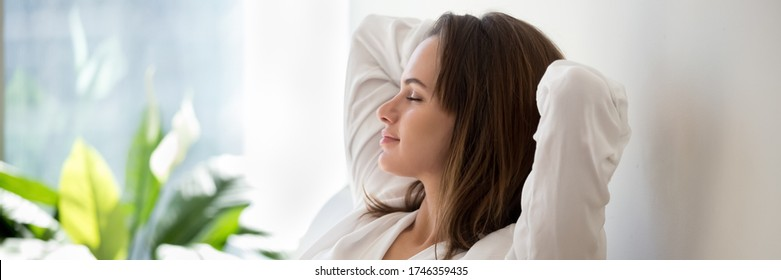 Beautiful 30s woman closed eyes put hands behind head relaxing on comfortable sofa in cozy warm light living room with houseplants, no stress concept, horizontal photo banner for website header design - Shutterstock ID 1746359435