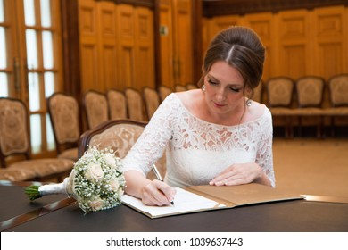 A beautiful 40 year old bride signs in a marriage registration book
