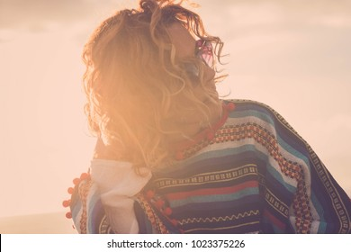 beautiful 40 years old woman look at her side touching his hair. Sunglasses and poncho in hippy style for freedom concept. Backlight with sunset
