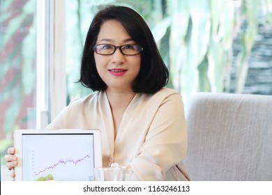 Beautiful 40s Asian woman smile and show her turnover or profit chart on tablet monitor,with tea cup.Looks smart and successful.Concept of modern Japanese housewife.