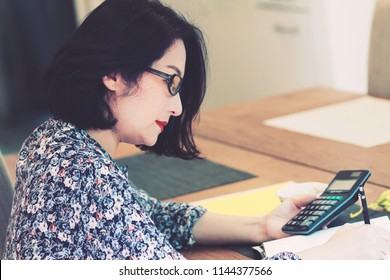 Beautiful 40s Asian woman wearing eye glass,working at  dining table.Using tablet,calculator and making note by pencil with tea cup.Looks smart and successful.Concept of modern housewife.Vintage tone.