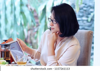 Beautiful 40s Asian woman wearing eye glass,working at dining table.Using tablet that show her turnover or profit chart with tea cup.Looks smart and successful.Concept of modern Japanese housewife.