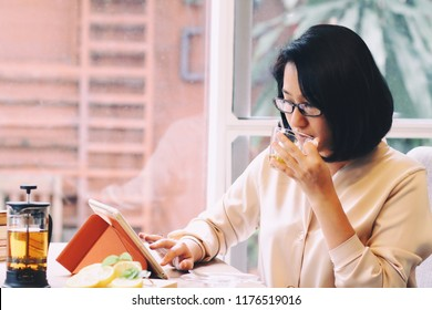 Beautiful 40s Asian woman wearing eye glass,working at dining table.Drinking tea,using tablet for information or study or investing.Looks smart and successful.Concept of modern Japanese housewife.