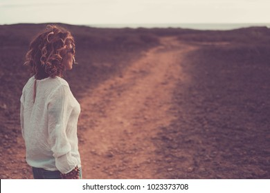 beautiful 4o years old woman with swirl brown hair walking on a path in a desert ground with ocean view. Lonely soul concept of exploration.