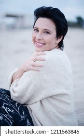 Beautiful 50 years old woman having cold in the winter beach, selective focus