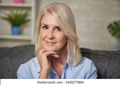 Beautiful 50 years old woman relaxing on sofa at home