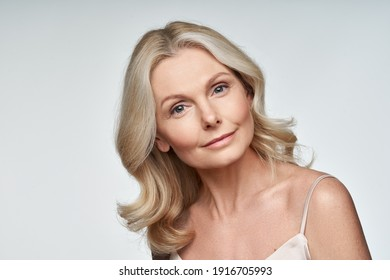 Beautiful 50s middle aged mature woman looking at camera isolated on white. Mature old lady close up portrait. Anti age healthy face skin care beauty, older skincare cosmetics, and cosmetology concept