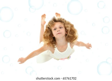 Beautiful 7 year old girl in white dress swimming over white with blue bubbles.