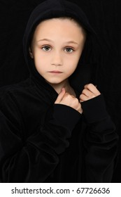 Beautiful 7 year old girl in black with worried expression.