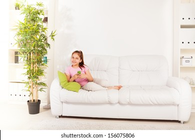 Beautiful 9 years old beautiful Caucasian girl texting on cell phone laying on the the couch in living room