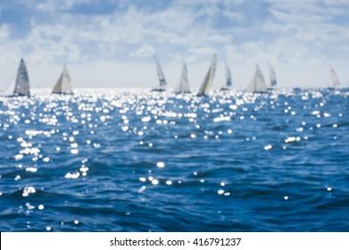 Beautiful abstract background bokeh sun light reflections on blue aqua water sailing boat