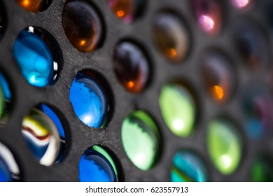Beautiful abstract background image of colorful vintage glass marbles in a metal display case with use of soft focus, blurring out the background & foreground around the main focus point