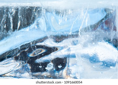 Beautiful abstract blue texture of transparent winter ice with rainbow colors