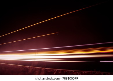 Beautiful, abstract car lights on a country road. TRaffic in the night, looking from a roadside. Long exposure photo.