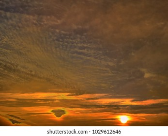 The beautiful abstract complex mixed image of the clouds over the lake of the City Park at the spring sunset.