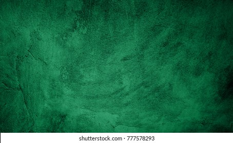 Beautiful Abstract Grunge Decorative Green Dark Stucco Wall Background. Art Rough Stylized Christmas Texture Banner With Space For Text. Textured background with bright center spotlight