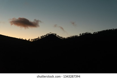 a beautiful abstract landscape in triangle shape - silhouette of mountains and trees before sunset with copy space