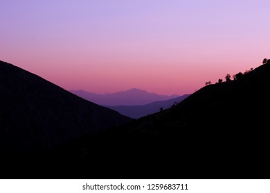 beautiful abstract nature sunset landscape with pink evening light between symmetry mountain range silhouettes, wallpaper background pattern concept with empty space for copy or your text