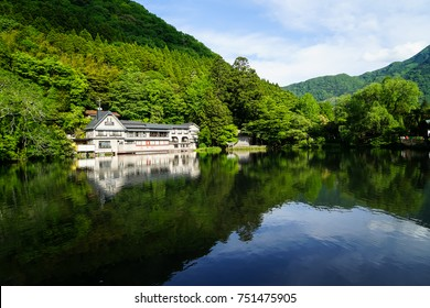 Beautiful abundant natural green mountain landscape symmetrical reflection on fresh lake Kinrin with buildings during springtime, Yufuin, Japan