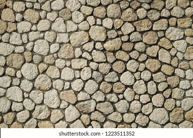 Beautiful accurate textured brick wall on bright sunny day. Stone background.
