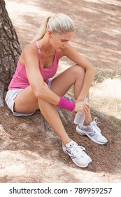 Beautiful active woman sitting on park floor by tree, resting drinking bottle of mineral water, recovering from exercising, outdoors. Mature female doing sport, healthy body recreation lifestyle.