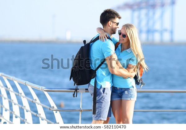 Beautiful active young couple in love, man and woman standing back to camera, looking ahead to sea, smiling, laughing and hugging, holding hands and standing on pier in background of  sea outdoor