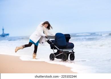 Beautiful active young mother walking on a beach pushing an all terrain double stroller with two children, baby and toddler, on a cold winter day in Holland
