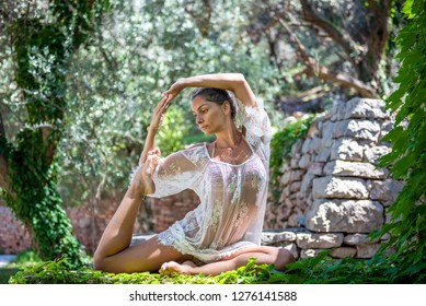 Beautiful, active, young woman dressed in white romantic blouse practicing yoga outdoor in nature. Concept: healthy life, self care, spring resolution, recreation, new beginning, mermaid pose