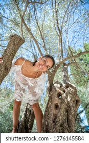 Beautiful, active, young woman dressed in white romantic blouse on olive tree, outdoor in nature. Concept: healthy life, self care, spring resolution, recreation, new beginning, nature lover, smiling