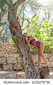 Beautiful, active, young woman dressed in colorful swim suit on olive tree, outdoor in nature. Concept: healthy life, self care, spring resolution, recreation, new beginning, nature lover, smiling