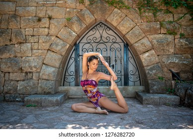 Beautiful, active, young woman dressed in colorful swimming suit, practicing yoga outdoor in nature. Concept: healthy life, self care, spring resolution, recreation, new beginning, mermaid pose