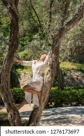 Beautiful, active, young woman in white romantic dress on olive tree, outdoor in nature. Concept: healthy life, self care, spring resolution, recreation, new beginning, nature lover, summer vibes, fun