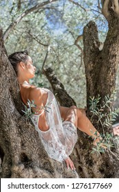 Beautiful, active, young woman in white romantic blouse on olive tree, outdoor in nature. Concept: self care, spring resolution, new beginning, nature lover, summer vibes, alone time