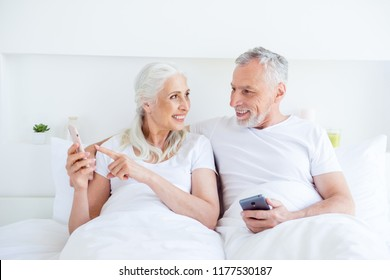 Beautiful, adorable, good-looking, grandma, granddad gray hair people, person show each other news on the smartphone screen lying in bed in bright white linen, sheets room interior