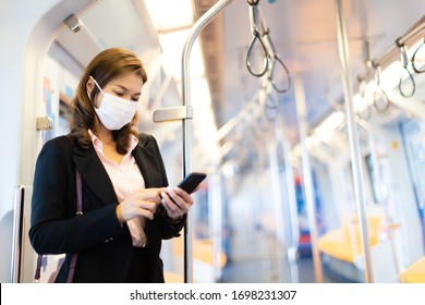 Beautiful adult Asian businesswoman passenger commuter wearing medical hygiene protect mask. Standing and using cell phone inside empty subway or sky train car. Idea for abandoned city from COVID-19.