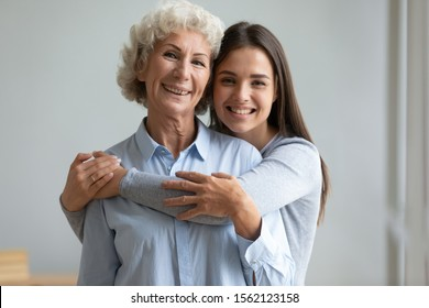 Beautiful adult daughter hug older mother at home, senior lady grandmother and young teen granddaughter embrace together, happy female two age generation family love care tenderness concept, portrait