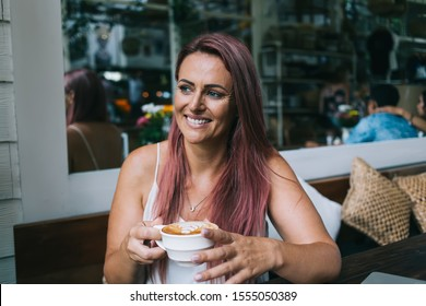 Beautiful adult female in dyed pink hair smiling and looking away while sitting in cozy cafe and drinking fresh latte