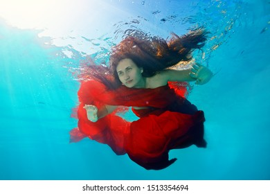 A beautiful adult girl dives under the water, to the bottom, with a red cloth wrapped around her body and with long loose hair that is illuminated by sunlight. Surreal portrait
