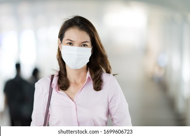 Beautiful adult middle age Asian working office businesswoman wearing surgical protective medical mask on face looking straight to camera while walking in path way to work in office. Health care idea.