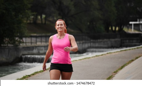 Beautiful adult red haired woman athlete in pink top and shorts makes amorning run on the city bridge over the river. Healthy lifestyle, jogging
