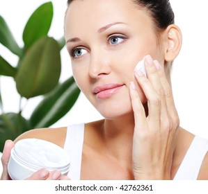 Beautiful adult woman applying moisturizer cream for her pretty face