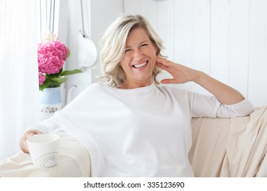 beautiful adult woman with blond hair, smiling, happy drinking coffee, tea.He is sitting on the sofa with a cup in hand.