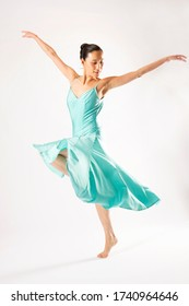 Beautiful adult woman dancer in shiny blue dress, dancing barefoot in the studio against a white background.