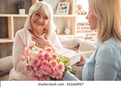 Beautiful adult woman is giving flowers and a gift box to her mature mother and smiling while sitting on couch at home