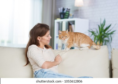 Beautiful adult woman at home on the couch with a pet redhead cat