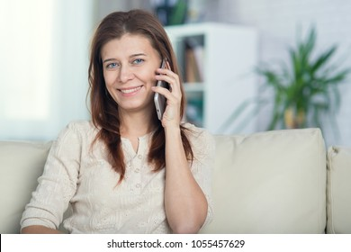 Beautiful adult woman at home on the couch talking on cell phone
