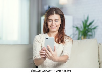 Beautiful adult woman at home on the couch do selfie  on cell phone
