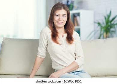 Beautiful adult woman at home on the couch alone on the window background